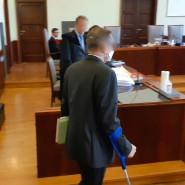 Der ehemalige Bankberater steht im Gerichtssaal, stützt sich dabei auf eine Krücke.