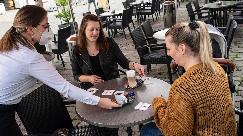 Kellnerin bedient im Außenbereich eines Cafés mit FFP2-Maske.