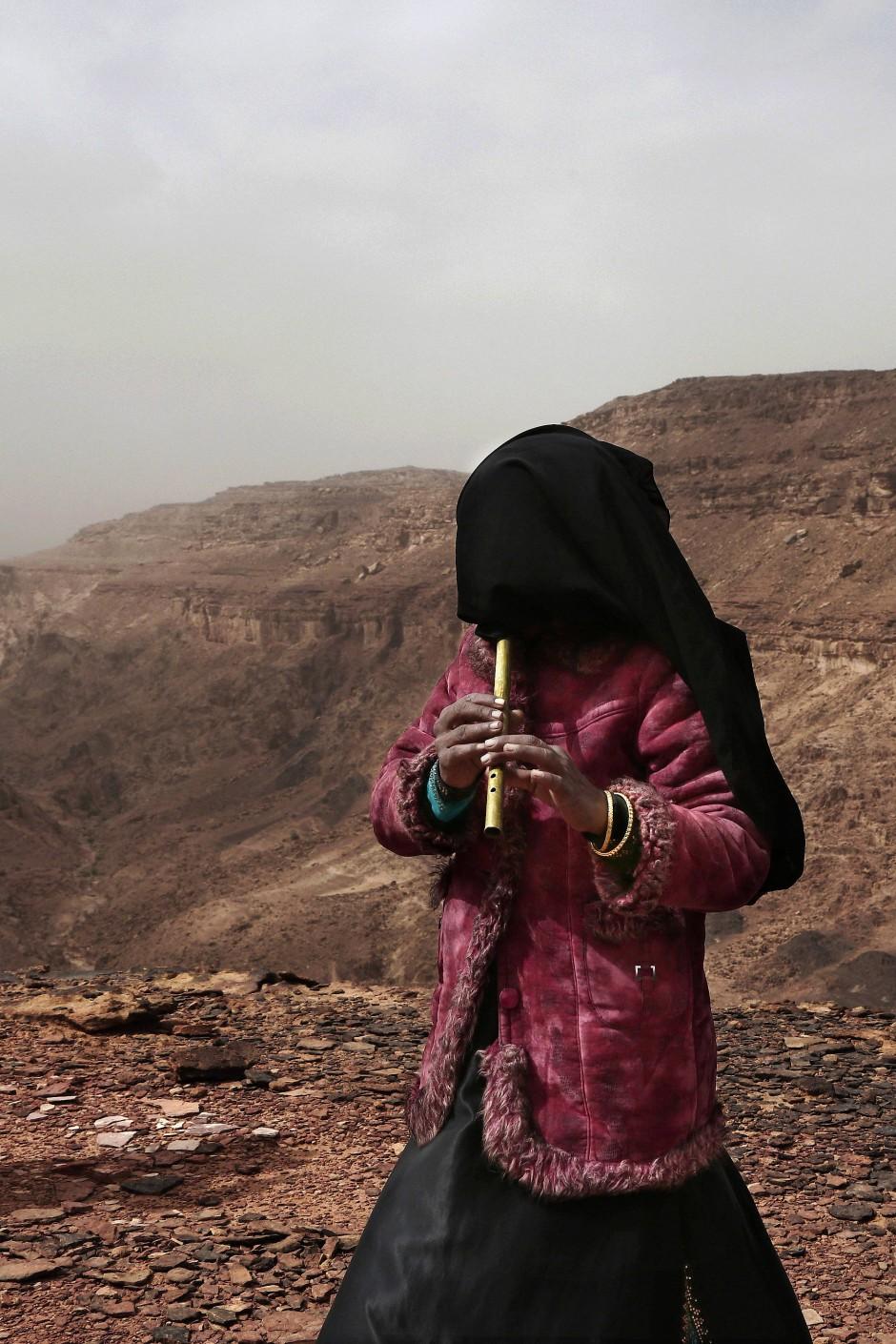 Aicha, eine weitere beduinische Wanderführerin, spielt während einer Pause den Touristinnen auf der Flöte vor. Der Gesichtsschleier schützt auch vor fliegendem Sand und Staub.