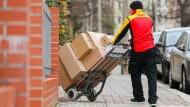 Ein Paketzusteller geht mit einer Sackkarre voll Pakete zu einem Haus in Halle.