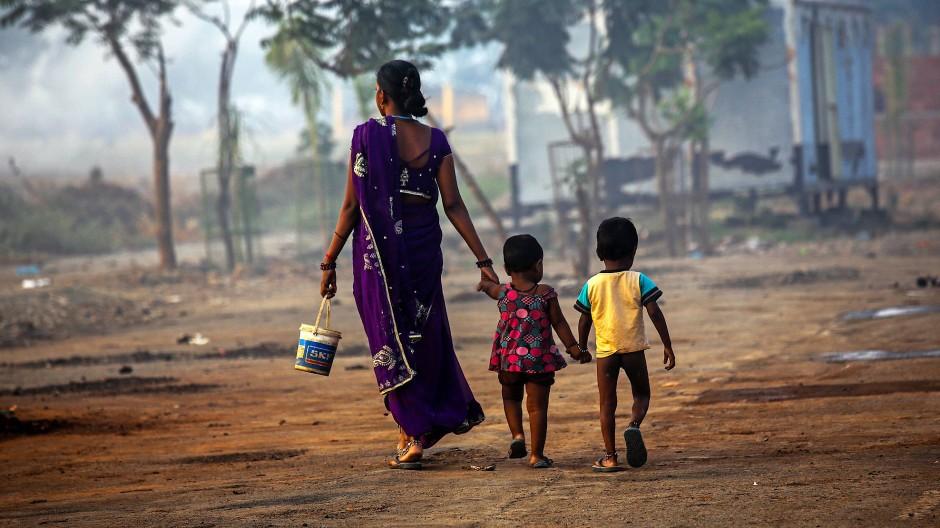Kaum Zugang zu sanitären Anlagen: Eine Frau geht am Rande von Mumbai zusammen mit ihren Kindern zu einer Latrine im Freien.
