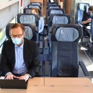 Ein Zugreisender trägt einen Mund-Nasen-Schutz.