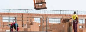 Maurer arbeiten am Rohbau von Reihenhäusern in einer Neubausiedlung in Regensburg.