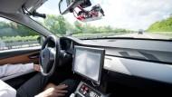Ein Bosch-Mitarbeiter fährt mit dem Prototyp eines autonomen Fahrzeugs. Bosch will mit Daimler zukünftig autonome Shuttles bauen.