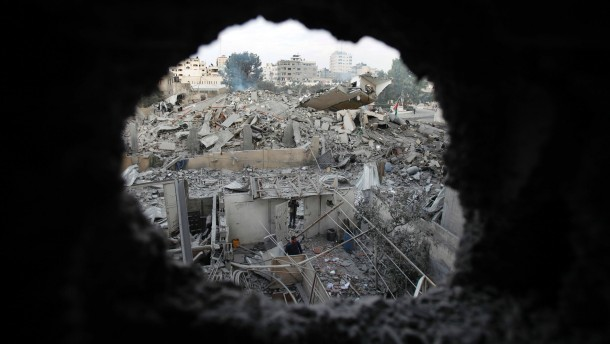 Palestinians are seen through a hole in the wreckage as they inspect the destroyed office building of Hamas PM Haniyeh in Gaza