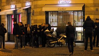 Polizeiermittler stehen vor dem Juweliergeschäft, in dem sich der Raub zutrug.