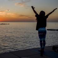 Eine Frau macht in Barcelona Yoga während eines Sonnenuntergans über dem Mittelmeer.