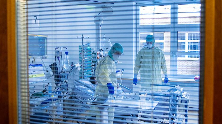 Mediziner und Pfleger versorgen einen an Covid-19 erkrankten Patienten in der Intensivstation des Universitätsklinikums Greifswald.