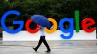Ein Mann läuft am Logo von Google vorbei.