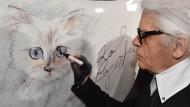 """Karl Lagerfeld malt 2015 bei der Vernissage """"Corsa Karl und Choupette"""" in Berlin."""