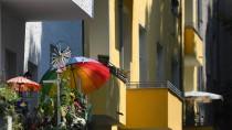 Ein bunter Sonnenschirm steht in Berlin auf einem geschmückten Balkon.