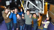 Azadeh Fattahi (on the right) and other students, standing by the telescope at the University of Victoria Observatory.