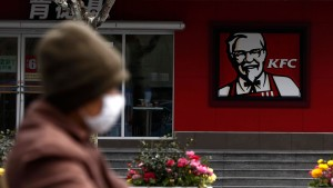 A woman, wearing a mask, rides past a KFC restaurant in Shanghai