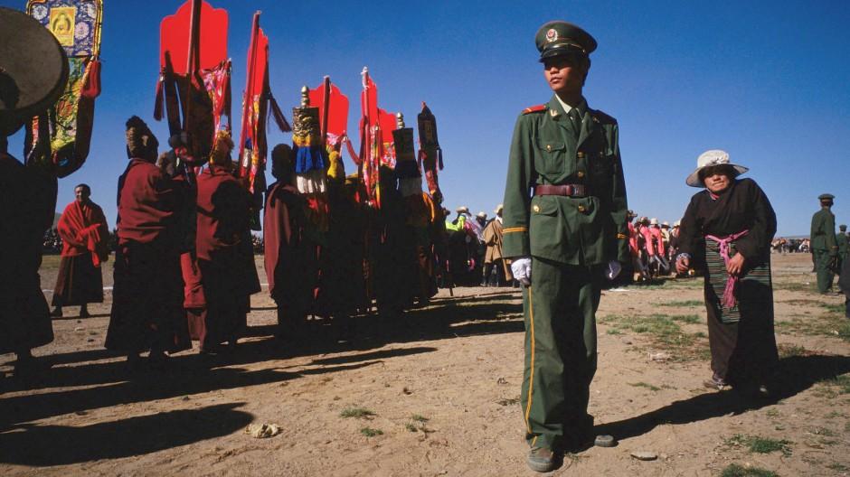 Die Kampflinie in Tibet verläuft zwischen Mönchen und chinesischer Armee: Ein Soldat der Volksbefreiungsarmee überwacht eine Prozession