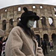 Eine chinesische Touristin trägt beim Besuch des Kolosseums in Rom Mundschutz: In Italien ist der erste Europäer an dem neuartigen Coronavirus gestorben.