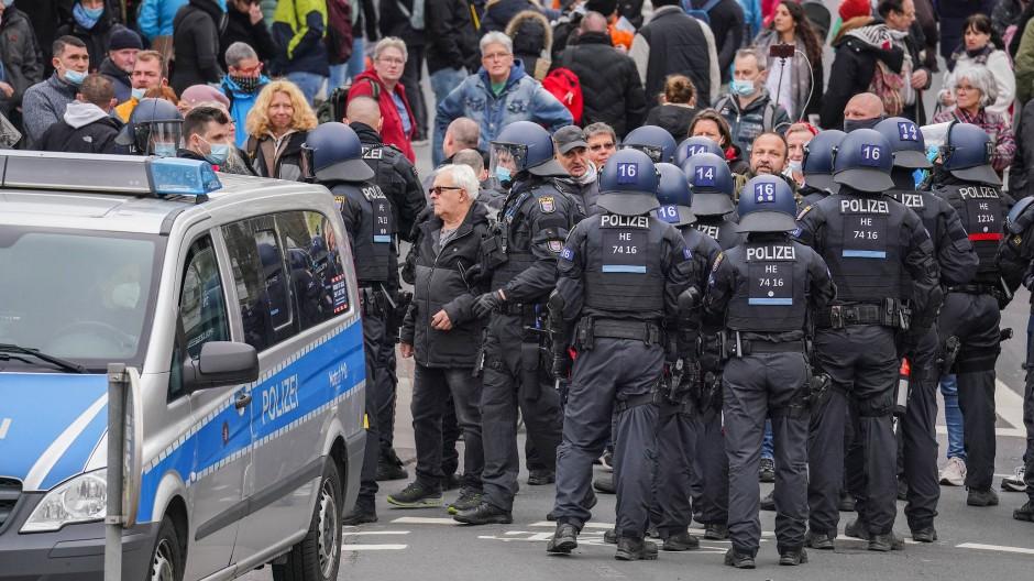 """Wiesbaden: Einsatzkräfte der Polizei stellen bei einer Kundgebung der sogenannten """"Querdenker"""" Personalien fest."""