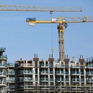 Kräne stehen auf einer Baustelle für Wohnhäuser in Hamburg.