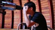 Wer durch's Teleskop schaut, der sieht bereits Vergangenes, wie hier ein Schüler in der Frankfurter Sternwarte.