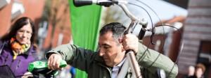 Cem Özdemir schiebt ein Fahrrad in eine automatische Fahrradwaschanlage.