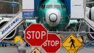 Eine Boeing 737 Max steht hinter Stopp-Schildern.
