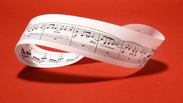 Möbiusband aus Musiknoten auf rotem Grund