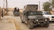 Gepanzerte Fahrzeuge der irakischen Armee fahren durch den Ort Bartella östlich von Mossul. Eine irakische Eliteeinheit hat den Ort vom IS befreit.