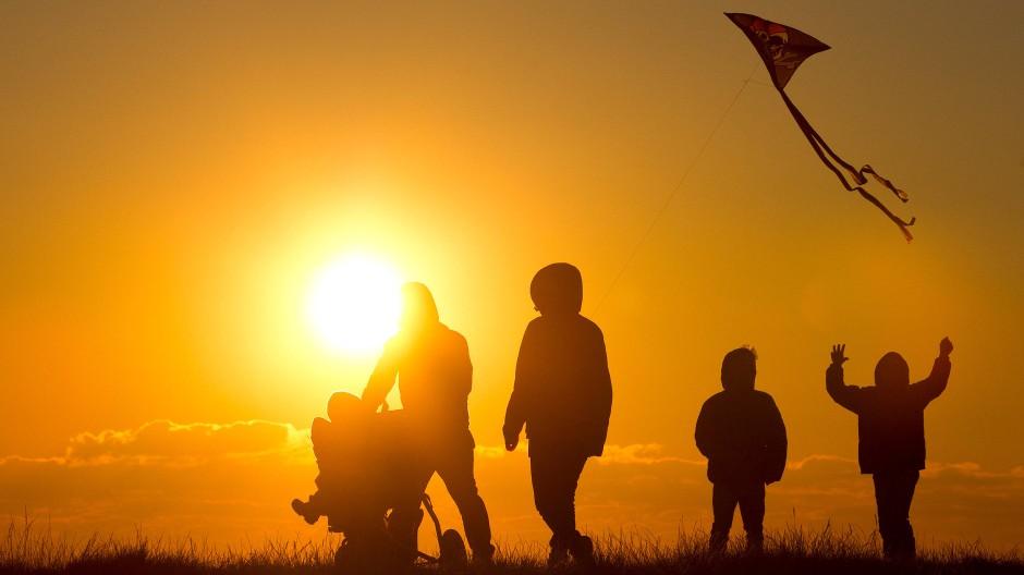 Familie mit Kinderwagen und Drachen bei Sonnenuntergang