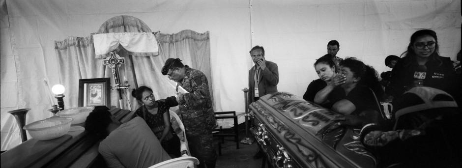 Ein Militärseelsorger besucht die Überlebenden Francisca Nij und ihren Bruder Francisco während der Totenwache für ihre Mutter.
