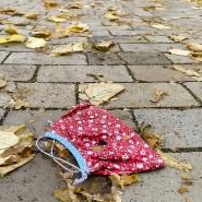 Ein Mund-Nasen-Schutz liegt auf dem Asphalt einer Einkaufsstraße.