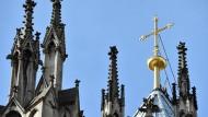 Ein goldenes Kreuz auf dem Kölner Dom leuchtet in der Sonne.