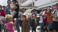 Kinder spielen, während Familien in der Schlange stehen, um von Hilfsorganisationen eine warme Mahlzeit zu erhalten.