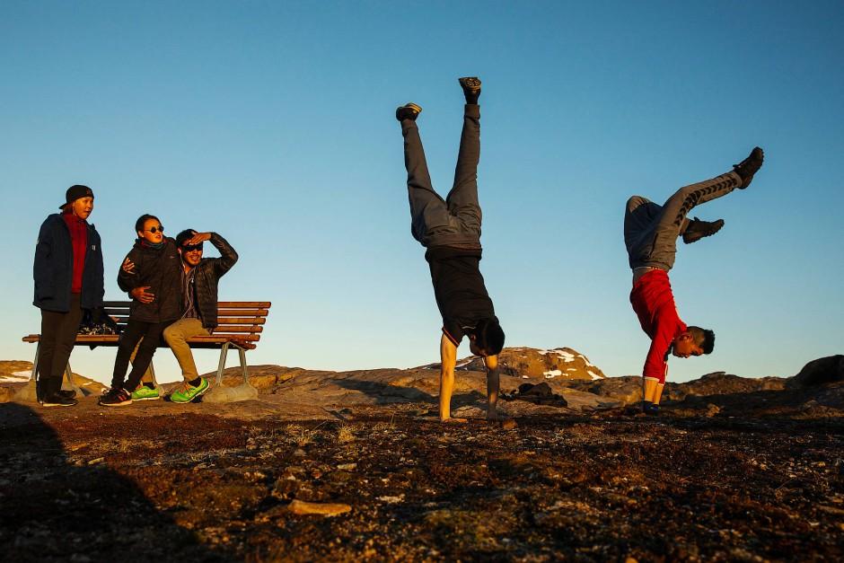 Grönlands Jugend feiert die letzten Sonnenstrahlen des Tages auf einem Hügel in der Nähe von Tasiilaq.