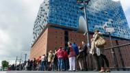Zahlreiche Menschen stehen vor der Hamburger Elbphilharmonie, um Karten für die Saison zu ergattern.
