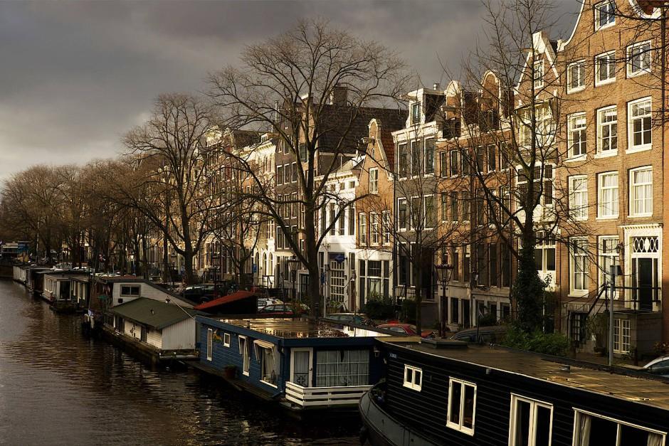 Hausboote und Wohnhäuser an der Prinsengracht: Die Innenstadt quillt über, sodass immer mehr Wohngebiete in den Randbezirken aus dem Boden gestampft werden.