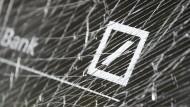 Unmut im Geldinstitut: Das Logo der Deutschen Bank hinter einer zerstörten Fensterscheibe