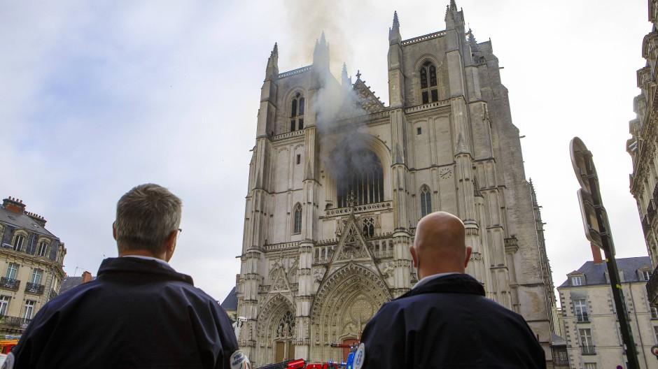 Die Polizisten in Nantes, die die Straßen für den Einsatz der Feuerwehr am Samstag absicherten, konnten nur zuschauen, wie Rauch aus einem Fenster der Kathedrale Saint-Pierre-et-Saint-Paul steigt.