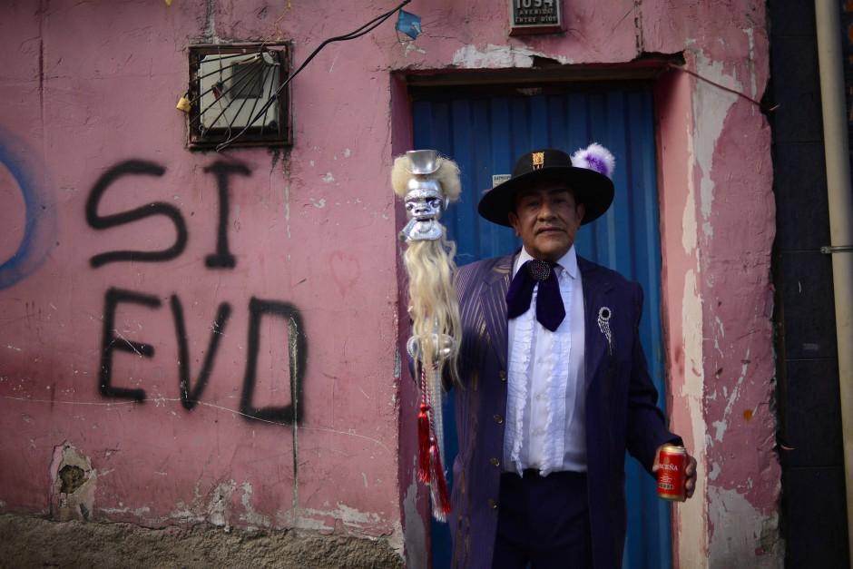 Ein Tänzer des Preste-Fests präsentiert sich in seinem Kostüm vor der Kamera. Im Hintergrund sieht man einen alten Schriftzug auf der Mauer, der zur Wahl und Unterstützung von Evo Morales aufruft.