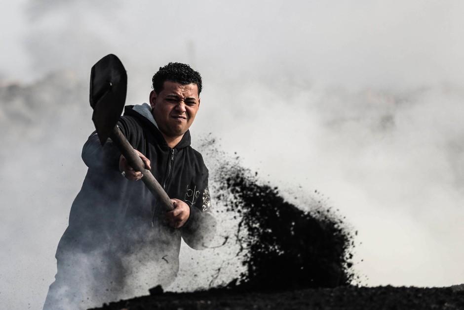 Das brennende und schwelende Holz muss kontinuierlich gewendet und gelüftet werden, damit Kohle entstehen kann.
