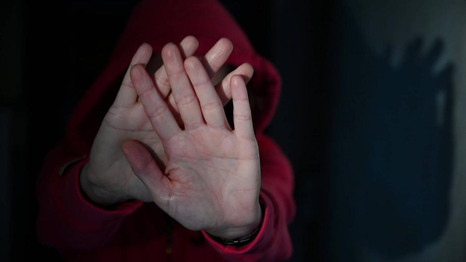 Gestellte Szene: Jemand versucht sich mit erhobenen Händen zu schützen.