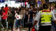 Reisende stehen am Kölner Hauptbahnhof hinter einem Absperrband der Polizei.