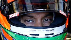 HRT Formula One driver Karthikeyan sits in his car during the third practice session of the Australian F1 Grand Prix at the Albert Park circuit in Melbourne