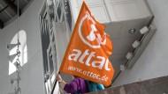 Eine Aktivistin hält eine Fahne mit dem Logo von Attac.