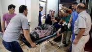 Eine bei dem Anschlag verwundete Frau wird ins Krankenhaus getragen.