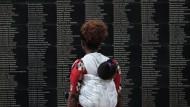 An einer Gedenkstätte in der Nähe Kigalis liest eine Frau die Namen der Opfer des Völkermordes.