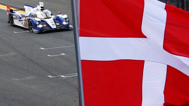 Nakajima of Japan drives his Toyota TS 030 Hybrid Number 7 as a Danish flag is flown at half-mast during the Le Mans 24-hour sportscar race in Le Mans