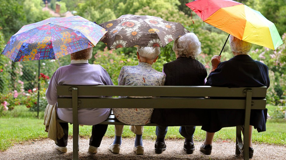 Seniorinnen sitzen im Baden-Badener Rosengarten Beutig auf einer Bank.