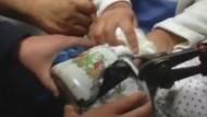 Kleines Kind steckt mit Kopf in Teekessel fest