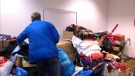Helfer sammeln warme Kleidung für Flüchtlinge