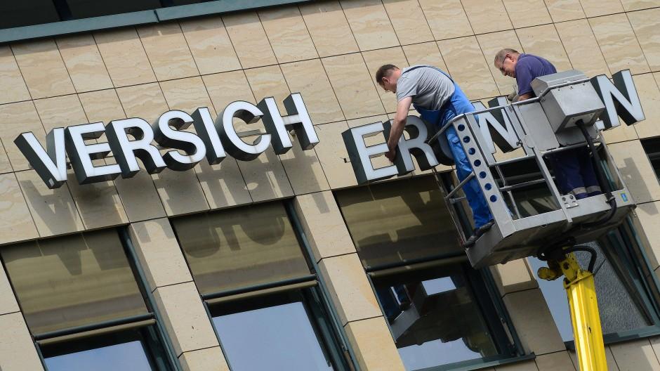 Zwei Männer wechseln an der Fassade eines Geschäftshauses in Kassel einen Teil des Schriftzuges «Versicherungen» aus.