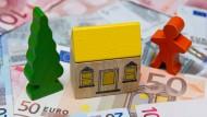 Unbezahlbar? Ein kleines Spielzeughaus steht auf Geldscheinen.